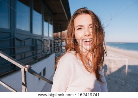 Smiling Woman in sweater standing on the beach near the cafe