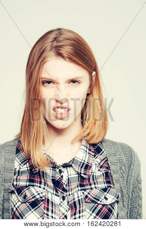 Dissatisfied pretty girl or cute beautiful woman female model with blonde hair in plaid shirt and knitted coat wrinkles nose on grey background