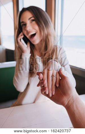 Vertical image of laughing woman on date talking at phone sitting by the table and holding hand her man. First-person view