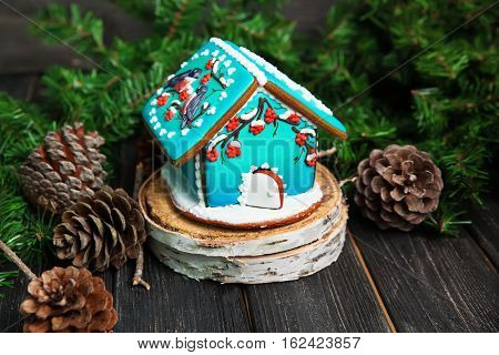 Christmas gingerbread house on wooden table, bullfinches and rowan decor.