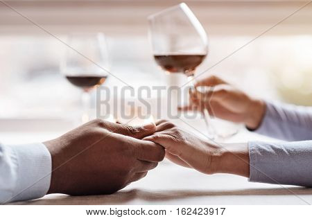 Time with my soulmate. Young positive peaceful African American couple sitting in the restaurant and having the date while expressing tenderness and enjoying the wine
