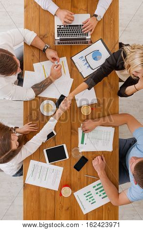 Agreement at business meeting. Busy people work in office, top view of wood table with mobile phones, laptop, tablet and documents papers with diagram. Women team handshake, have contract conclusion.