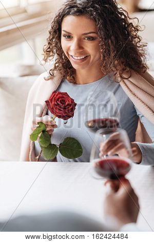 Delighted from the first date. Happy glad smiling African American woman sitting in the restaurant and looking at her boyfriend while expressing affection and holding red rose and wineglass