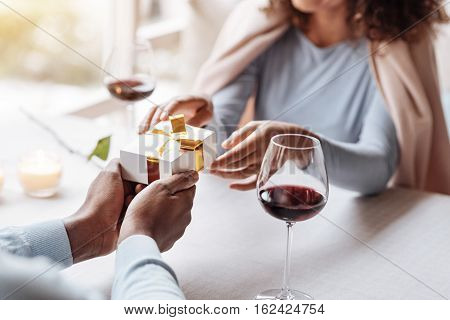 This present is for my love. Positive shy overwhelmed African American man sitting in the restaurant and spending the time with his girlfriend while expressing care and giving the present to her