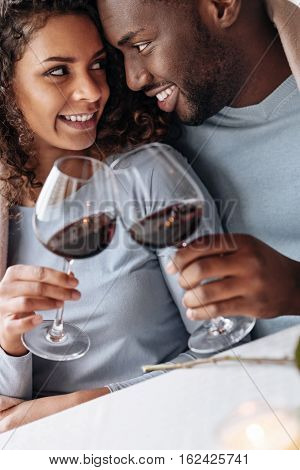 Infatuated with you. Passionate smiling delighted African American couple sitting in the restaurant and hugging each other while being covered with the blanket and drinking wine