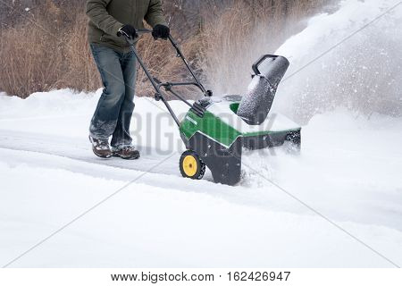 A snowblower in action being pushed during light snowfall