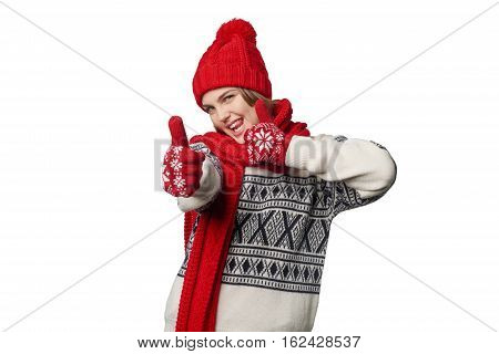 Excited winter warm clothing girl giving double thumb up, showing playful tongue, over white background