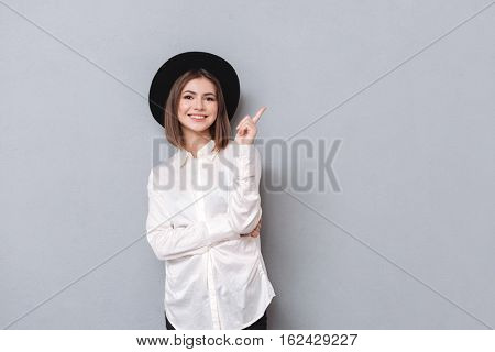 Portrait of a smiling young woman in hat pointing finger away and looking at camera isolated on the gray background