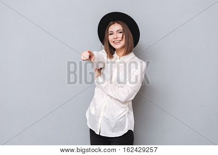 Portrait of a happy cheerful woman pointing finger at camera isolated on a gray background
