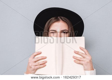 Close up portrait of a young woman in hat covering her mouth with book and winking isolated on the gray background