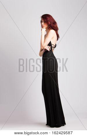 beautiful red-haired girl in long black evening dress studio shot