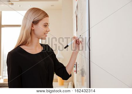Young businesswoman writing on flipchart while giving presentation to colleagues standing in office. Looking aside.