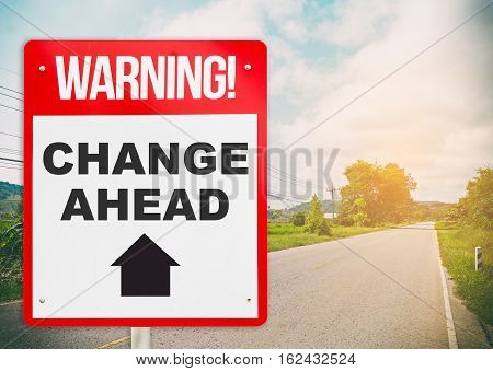 Warning sign on bright street saying Change ahead.