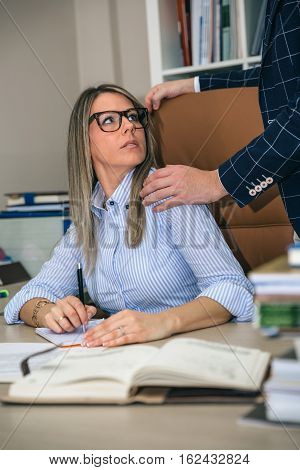 Portrait of shocked blonde secretary looking to boss putting hand over her shoulder in the office. Sexual harassment at work concept.
