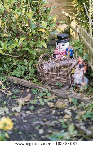 Snowman behind a rustic wicker basket outdoors covered in fallen leaves from an autumn tree in a concept of landscaping and decoration
