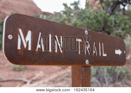 A brown metal sign directs hikers to the main trail in Arches National Park