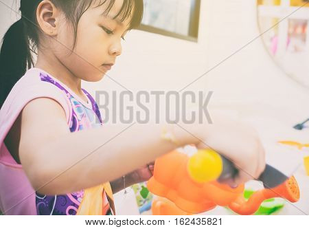 Asian girl playing with colorful sandbox toys.