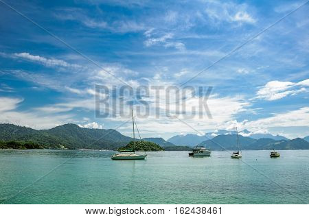 Boats floating in the turquoise water against the background of mountains and beautiful blue sky with spindrift clouds next to Ilha Grande, Angra dos Reis, RJ, Brazil