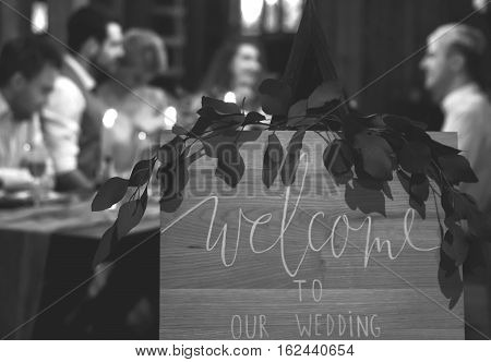 Wedding feast. Guests sit at festively decorated table. Evening candlelight. Black and white.
