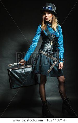 Journey and travel. Retro stylished girl with vintage big bag suitcase valise. Stylish victorian woman on dark background.