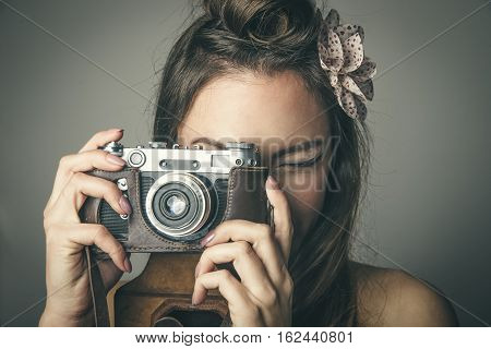 Close-up portrait of young Caucasian woman taking pictures with vintage camera against gray background