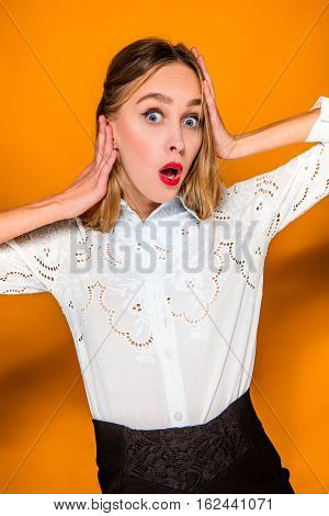 Portrait of young woman with shocked facial expression on orange studio background