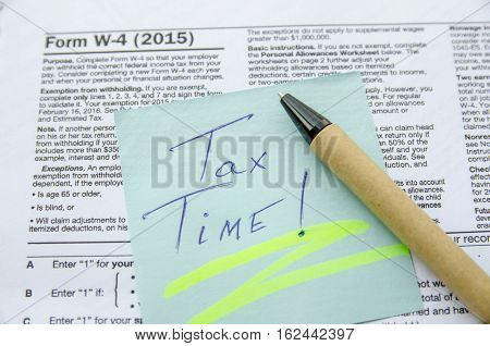 text tax time on notepad with Tax Form 4 W