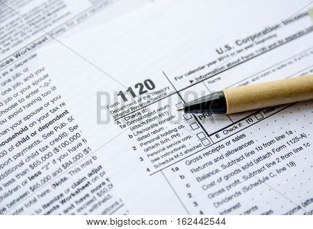 Form 1120 Corporate Tax Return with pen