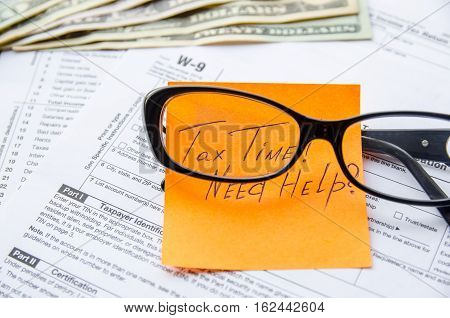W-9 tax form as a business concept with dollar and glasses