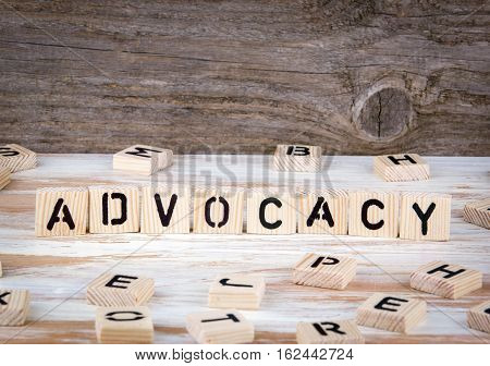 Advocacy from wooden letters on wooden background.