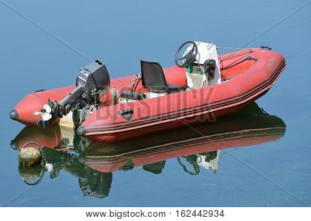 image of red inflatable boat with motor