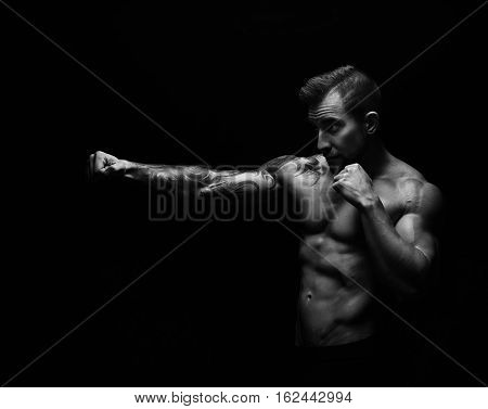 Athletic man make punch. Handsome fitness model show naked torso, muscular body. Strong muscles. Studio shot on black background, monochrome, black and white. Kickboxing and fight sport concept