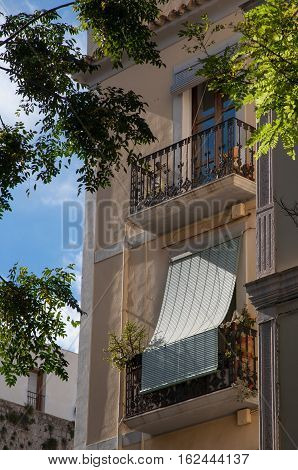 Traditional Spanish balconies with wrought iron balustrades in the afternoon sun