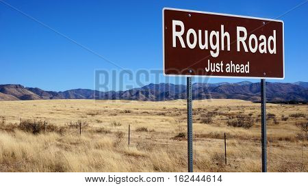 Rough Road road sign with blue sky and wilderness
