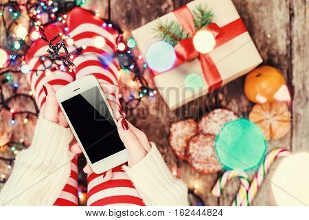 Cozy Christmas at home. Female hands holding mobile phone. Women's feet in Christmas stockings big present on bokeh light background. Top view. Selective focus. Toning