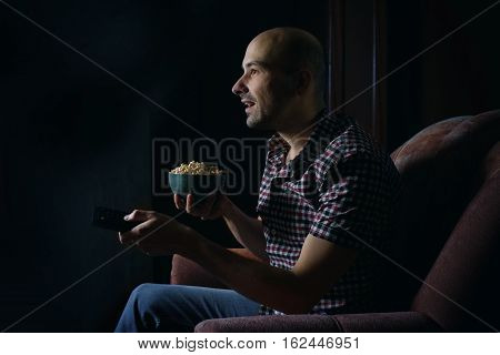 Guy Watching Tv With Remote Control At Night