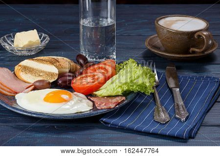 Substantial breakfast with fried egg salad bacon bread and coffee