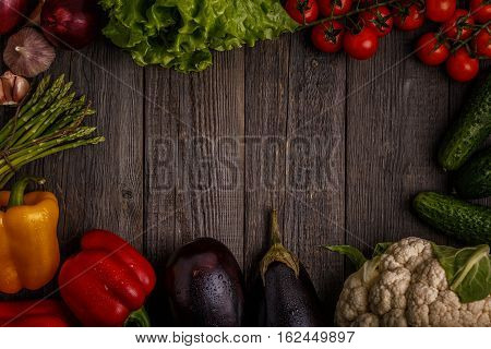 Fresh vegetables for cooking on dark wooden background with space for text. Top view. Concept of healthy vegetarian diet food.