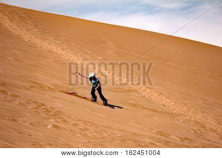SAN PEDRO DE ATACAMA, CHILE-NOV.10,2016: A sand boarder zips along the red sands of Death Valley in Chile's Atacama Desert.