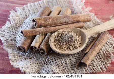 ground cinnamon and cinnamon sticks close-up dry