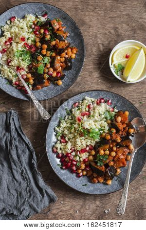 Moroccan aubergine and chickpea stew and bulgur. Healthy vegetarian lunch. On a wooden table top view. Flat lay