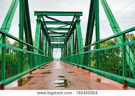 Pedestrian iron bridge over the river on a rainy day