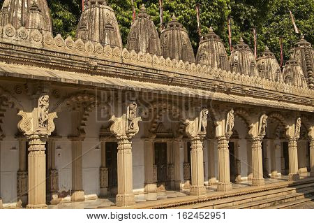 AHMADABAD, INDIA - OCTOBER 30, 2007: Ornately carved stonework of a colonnade surrounding the courtyard of the Hutheesing Temple in Ahmadabad, Gujarat, India. Jain temple built circa 1848.