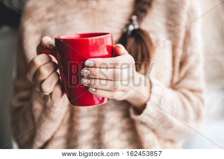 Woman's hand holding a red cup of coffee. With a beautiful winter manicure. Drink fashion morning