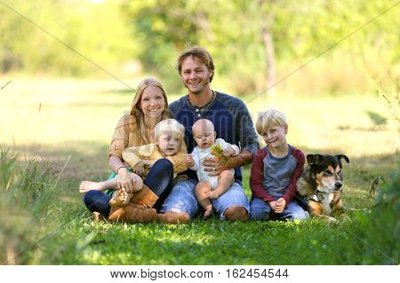 A happy family of five people including mother father new baby boy and his brother are sitting outside in the sunny garden with their adopted German Shepherd dog.