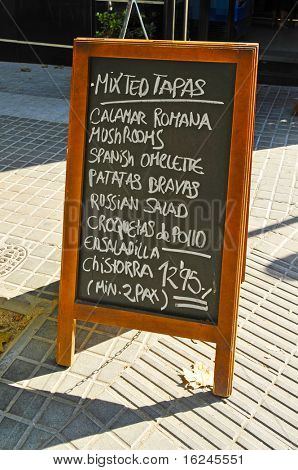 a blackboard menu on a restaurant terrace