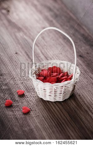 Busket with red hearts on wooden bakground. Love concept.