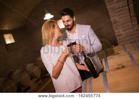 Cute people tasting wine in winery basement