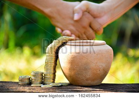 The old earth ware and coin stack almost drop in earth ware and hand of people shake hand
