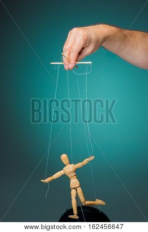 Image puppet in the hands of the puppeteer on blue background